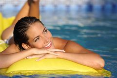 Muchacha que disfruta de vacaciones de verano en un colchón en una piscina y que mira el lado Foto de archivo libre de regalías