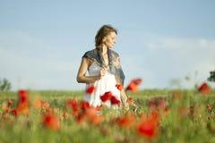 Muchacha que disfruta de verano en un campo de la amapola Imagen de archivo libre de regalías