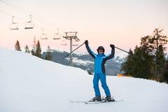 Muchacha que disfruta del día de fiesta del esquí que se coloca en la montaña nevosa Fotografía de archivo libre de regalías