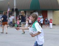 Muchacha que distribuye el caramelo en un desfile en la pequeña ciudad América Imágenes de archivo libres de regalías
