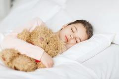 Muchacha que duerme con el juguete del oso de peluche en cama en casa Imagenes de archivo