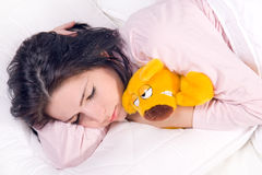 Muchacha que duerme con el oso de peluche Fotografía de archivo libre de regalías