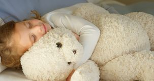 Muchacha que duerme con el oso de peluche en el dormitorio 4k almacen de metraje de vídeo
