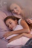 Muchacha que duerme con la madre Imagen de archivo