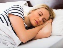 Muchacha que duerme con pygamas rayados en cama Fotografía de archivo