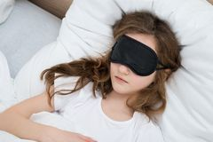 Muchacha que duerme en cama con la máscara del sueño fotos de archivo