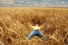 Muchacha que duerme en el campo de trigo en el verano. Foto de archivo