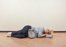 Muchacha que duerme en el piso el cuarto vacío Imagenes de archivo
