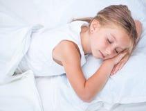 Muchacha que duerme en la cama blanca Fotografía de archivo libre de regalías
