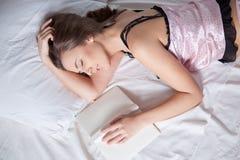 Muchacha que duerme en la cama con un libro Fotos de archivo