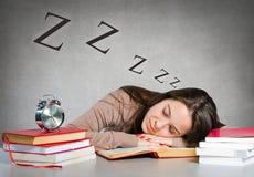 Muchacha que duerme en los libros Foto de archivo