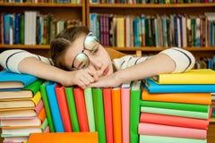 Muchacha que duerme en los libros en la biblioteca imagenes de archivo