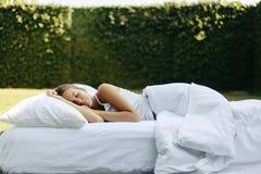 Muchacha que duerme en matress en hierba fotografía de archivo libre de regalías