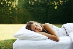 Muchacha que duerme en matress en hierba foto de archivo libre de regalías