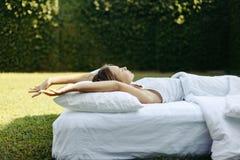 Muchacha que duerme en matress en hierba imagen de archivo libre de regalías