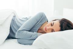 Muchacha que duerme en su cama Foto de archivo libre de regalías
