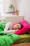 Muchacha que duerme en su cama en casa Imágenes de archivo libres de regalías