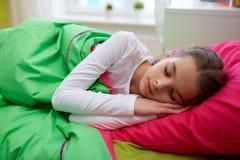 Muchacha que duerme en su cama en casa Imagenes de archivo