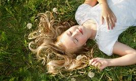 Muchacha que duerme en un campo de la hierba Fotografía de archivo