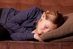 Muchacha que duerme en un sofá Imagen de archivo libre de regalías