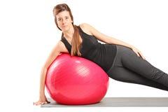 Muchacha que ejercita con la bola de los pilates en la estera del ejercicio Fotografía de archivo