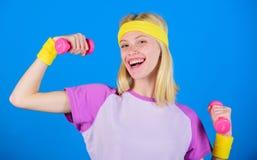 muchacha que ejercita con pesa de gimnasia Instructor de la aptitud llevar a cabo poco fondo azul de la pesa de gimnasia Cómo con imagen de archivo