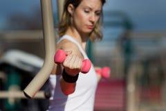 Muchacha que ejercita con pesas de gimnasia Fotos de archivo libres de regalías