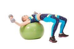 Muchacha que ejercita con pesas de gimnasia en bola de la aptitud Imagenes de archivo