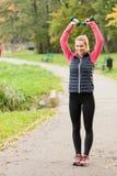 Muchacha que ejercita con pesas de gimnasia en parque Fotografía de archivo libre de regalías