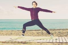 Muchacha que ejercita en la estera del ejercicio al aire libre Fotografía de archivo