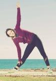 Muchacha que ejercita en la estera del ejercicio al aire libre Imágenes de archivo libres de regalías