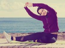 Muchacha que ejercita en la estera del ejercicio al aire libre Fotos de archivo libres de regalías