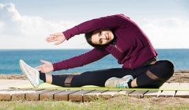 Muchacha que ejercita en la estera del ejercicio al aire libre Foto de archivo libre de regalías