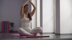 Muchacha que ejercita la yoga, tomando una posición del rezo metrajes