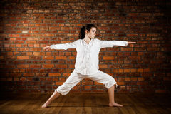 Muchacha que ejercita yoga contra la pared de ladrillo Foto de archivo