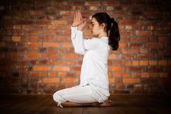 Muchacha que ejercita yoga contra la pared de ladrillo Fotos de archivo libres de regalías