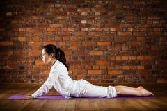 Muchacha que ejercita yoga contra la pared de ladrillo Fotografía de archivo