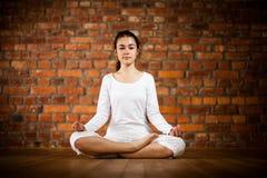 Muchacha que ejercita yoga contra la pared de ladrillo Imagen de archivo libre de regalías