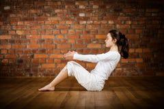 Muchacha que ejercita yoga contra la pared de ladrillo Fotografía de archivo libre de regalías