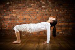 Muchacha que ejercita yoga contra la pared de ladrillo Imagenes de archivo