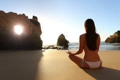 Muchacha que ejercita yoga en la playa en la puesta del sol Imagenes de archivo