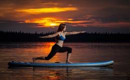 Muchacha que ejercita yoga en paddleboard en la puesta del sol en el lago escénico Velke Darko foto de archivo