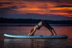 Muchacha que ejercita yoga en paddleboard en la puesta del sol en el lago escénico Velke Darko fotos de archivo libres de regalías