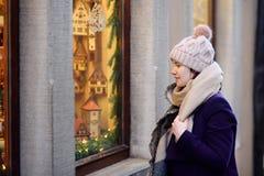 Muchacha que elige decoraciones de la Navidad en tienda el día de invierno Imagen de archivo