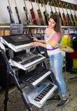Muchacha que elige el sintetizador en tienda Fotografía de archivo libre de regalías
