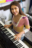 Muchacha que elige el sintetizador en tienda Foto de archivo