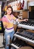 Muchacha que elige el sintetizador en tienda Imágenes de archivo libres de regalías