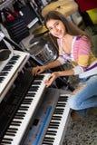 Muchacha que elige el sintetizador en tienda Fotos de archivo