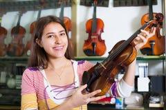 Muchacha que elige el violín en tienda de la música Imágenes de archivo libres de regalías