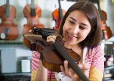 Muchacha que elige el violín en tienda de la música Fotografía de archivo